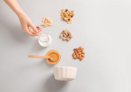 Female hand with jug of yogurt, tasty granola and ingredients on white background