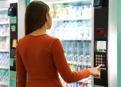 Young traveler woman choosing a snack or drink at vending machine in airport. Vending machine with girl.