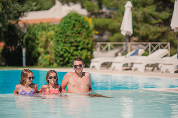 Happy family of three in outdoors swimming pool