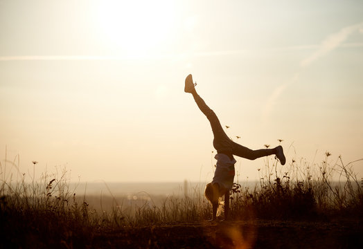 Young girl doing a handstand. Beautiful view horizon of a sunset on the background