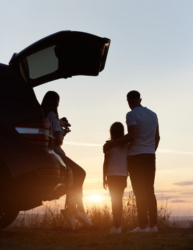 Silhouette of the family of three enjoying the sunset on the top of hill outside the city, woman is sitting in the car trunk, holding jack russell terrier, man is standing embracing his daughter
