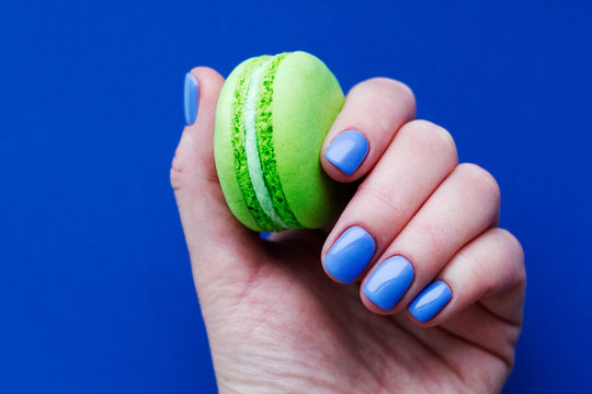 Hand with classic blue manicure with bright green macaron. Isolated at blue background.