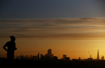 A man jogs as the sun rises behind the city of London financial district and The Shard in London
