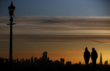 People watch the sun rise behind the city of London financial district and The Shard in London
