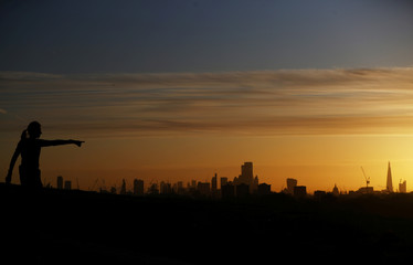 A woman watches the sun rise behind the city of London financial district and The Shard in London