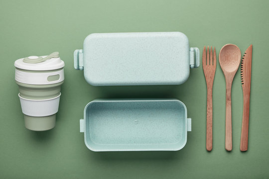 Zero waste lunch concept. Reusable cup and box, bamboo cutlery. Flat lay on green background