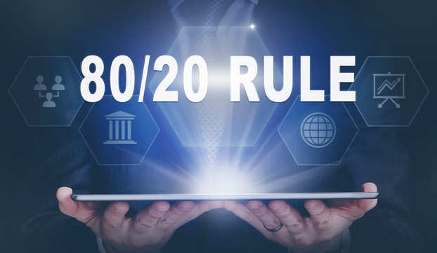 Businessman holding a computer tablet display projecting a 80 / 20 Rule concept.
