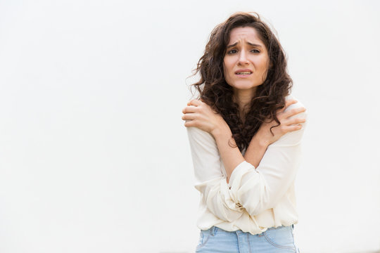 Desperate upset woman freezing, trembling, hugging herself for warm. Wavy haired young woman in casual shirt standing isolated over white background. Fever or fear concept