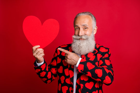 Photo of funky mature man cupid amour hold big paper heart shape indicating finger creative postcard wear stylish hearts pattern suit blazer shirt tie isolated red color background