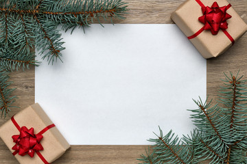 Christmas or New Year composition. White sheet of paper with copy space, gift boxes and Christmas tree branches on wooden background. Flat lay, top view, horizontal layout
