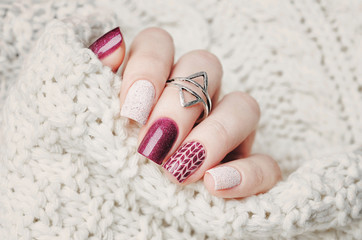 Photo sur Aluminium Manicure winter nail art manicure and knitted sweater on the background