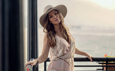 Portrait of sexy young woman looking at camera in stylish hat