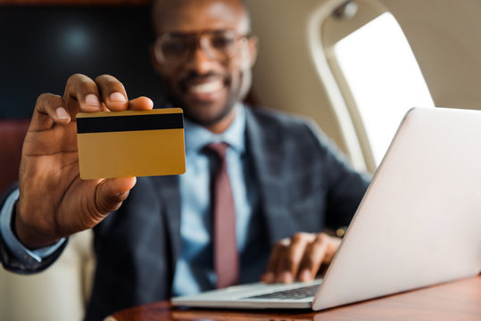 selective focus of african american businessman holding credit card near laptop in private plane