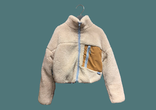 Beige faux suede and faux shearling jacket with contrasting details on hanger isolated on green background. Composition of clothes. Ladies' Trench Coat. Winter clothes pattern.