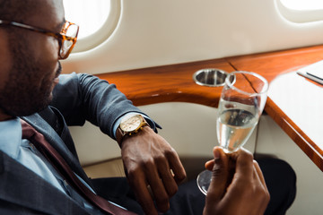 selective focus of african american businessman in suit holding champagne glass in private jet