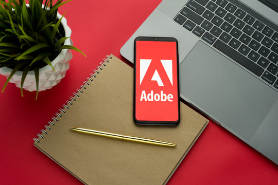 Tula, Russia, november 26, 2019: Adobe logo on the smartphone screen is placed on the Apple macbook keyboard on red desk background.