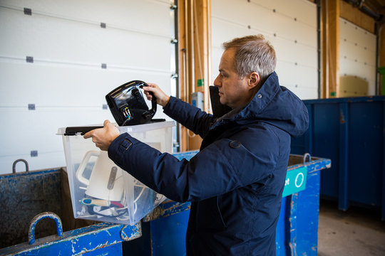 A man putting old appliances into dumpster in sorting centre for safe disposal and recycling