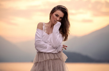 Portrait of sensual woman outdoor, posing at the sunset over mountains background