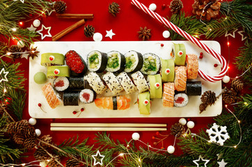 In de dag Sushi bar Christmas sushi set flatlay with Christmas decorations on red background