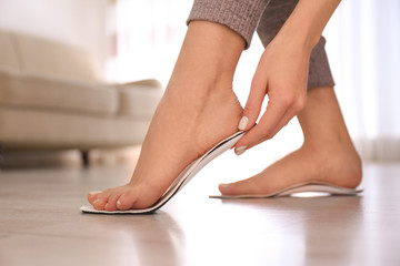 Woman fitting orthopedic insole at home, closeup