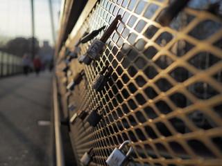 Love locks padlocks on bridge fence during sunset warm color