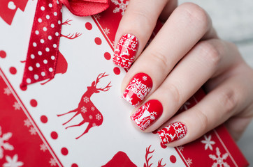 Foto op Canvas Manicure red Christmas manicure with deer and snowflakes and Norwegian pattern with box for gifts