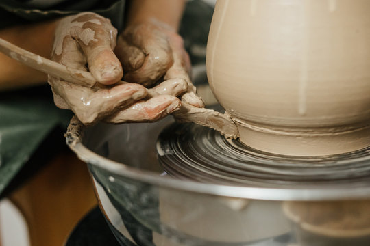Hands of potter making clay pot on potter's wheel
