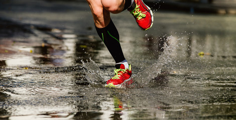 Fototapete - feet runner athlete run puddle on road, water splash