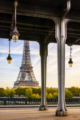 Fotobehang Eiffeltoren The Eiffel tower in Paris seen from the Bir-Hakeim bridge by a sunny morning with the glass globes of the Art Deco street lights and the metal pillars supporting the subway track in the foreground.