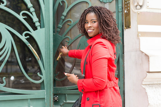 Woman opening door and smiling at camera. Cheerful young African American woman holding smartphone and entering building. Emotion and technology concept