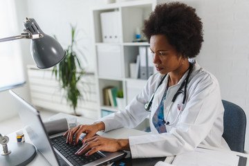 Serious concentrated African American doctor working in her office at clinic