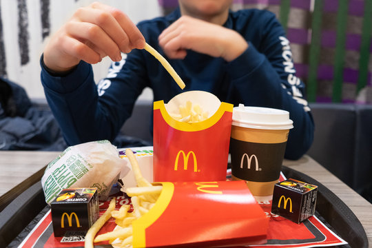 Minsk, Belarus. December, 2019. Popular fast food cafe McDonald's. Famous fries, tea, chickenburger in the original packaging. Favorite food of children and teenagers.