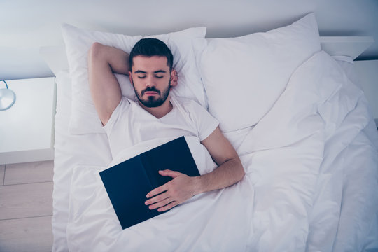 Top above high angle view portrait of his he nice attractive bearded guy lying on white bed resting sleeping peacefully fallen asleep holding in hand book at night late evening home room flat indoors