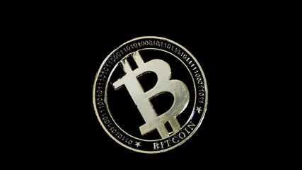 Shiny gold bitcoin virtual crypto currency coin laying on black background