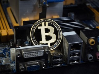 Shiny gold bitcoin virtual crypto currency coin laying on electronic circuit motherboard computer