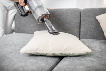 Woman cleaning sofa with a modern cordless vacuum cleaner with a special nozzle, close-up. Dry cleaning concept with wireless vacuum cleaner