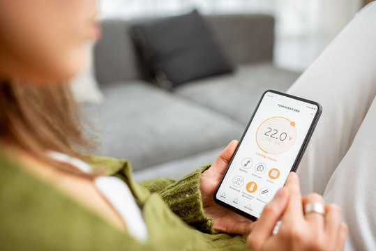 Controlling heating temperature with a smart phone, close-up. Concept of a smart home and mobile application for managing smart devices at home