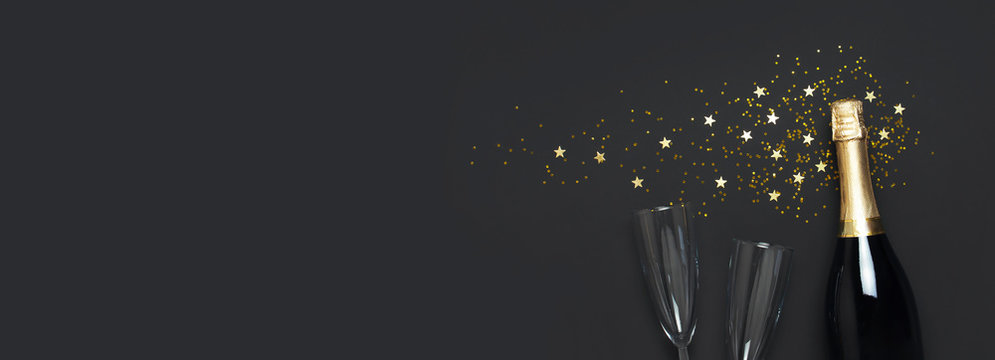 Christmas and New Year background. Champagne bottle, champagne glasses, festive golden star confetti on black background top view. Flat lay holiday card. Birthday or party concept. Festive decorations