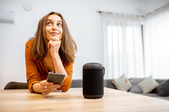Portrait of a young and cheerful woman with a smart wireless column and phone at home. Concept of smart home and voice command control