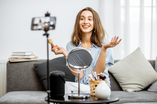 Young woman recording on a smart phone her vlog about cosmetics, showing and demonstrating makeup. Influencer marketing in social media concept