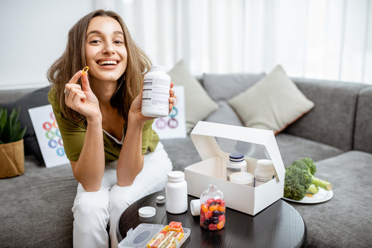 Portrait of a young smiling woman taking nutritional supplements at home. Concept of biohacking and preventive medicine