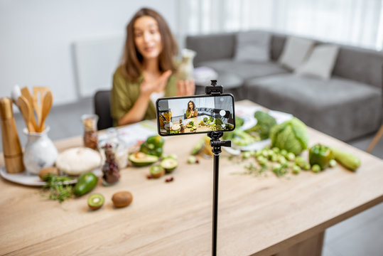 Young woman recording on a smart phone her vlog about healthy eating. Sitting at the table with lots of green vegan food ingredients at home