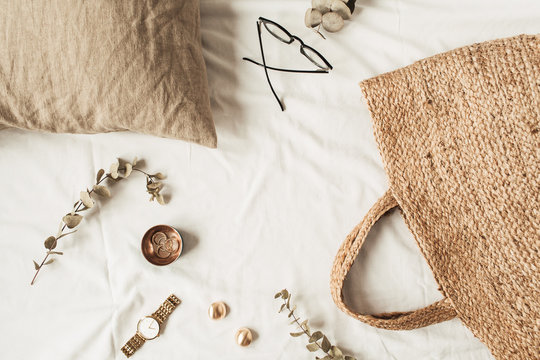 Frame with copy space made of fashion women accessories, straw bag, pillow, eucalyptus branches on white linen. Flat lay, top view blank mockup concept for social media, website, blog.