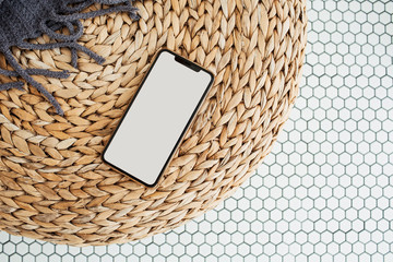 Blank screen cell phone with empty copy space mockup on rattan puff, plaid and mosaic tile. Flat...