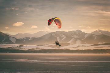 Foto auf Acrylglas Beige Motor paraglider over the lake with mountains and sky on background, winter sunset landscape, tourist attraction, Liptovska Mara, largest water reservoir in Slovakia (Slovensko), travel destination