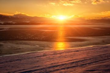 Fototapeten Dunkelbraun Winter golden sunset landscape with lake, snowy bank, mountains on background, sky with clouds and sun. Liptovska Mara, largest water reservoir (dam) in Slovakia (Slovensko), tourist destination