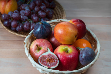 fresh fruits and red grape berries in a straw basket on a  wooden background