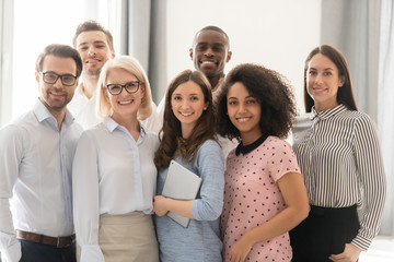 Smiling multiethnic employees posing together for group picture