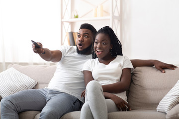 Excited afro couple watching tv together, sitting on couch at home Wall mural