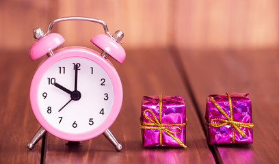 Time to gift, shopping concept, pink alarm clock and christmas gift boxes on wooden background, web banner